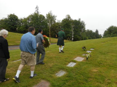 Piper Tim Leading, Followed By JJ Carrying The Wreath With Members Following